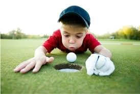 little boy blowing the golf ball into the hole
