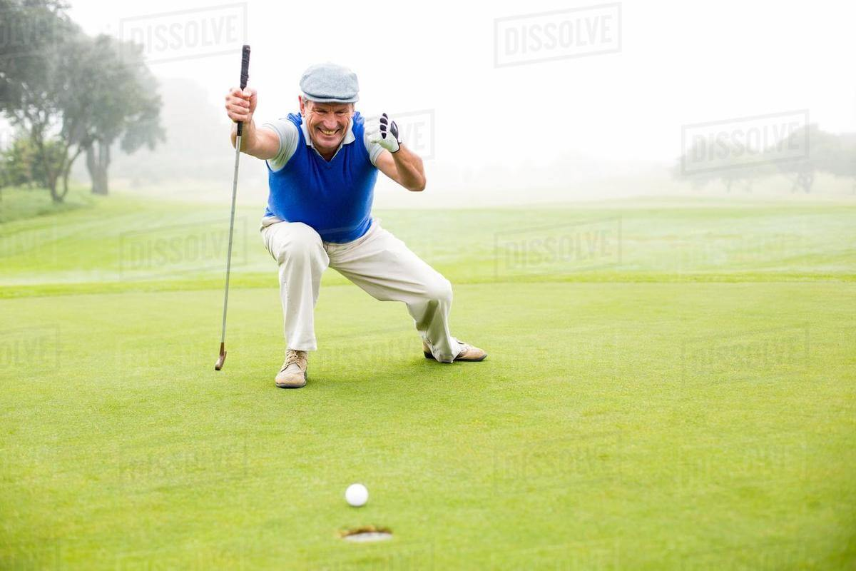 a golfer celebrating watching his putt