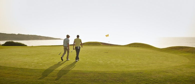 Two golfers walking on the green