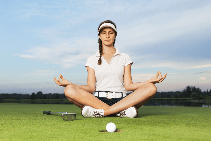 a woman mediating on a golf green
